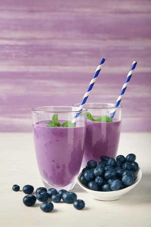 Glasses of tasty blueberry smoothie on table