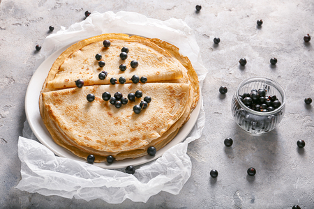 Delicious thin pancakes with currant on plate