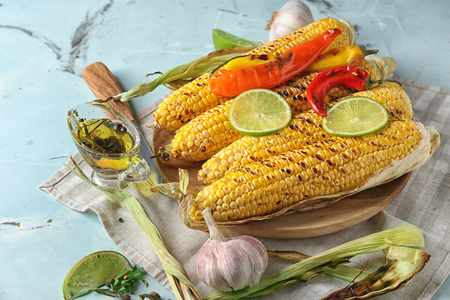 Grilled corn cobs on wooden plate Stock fotó