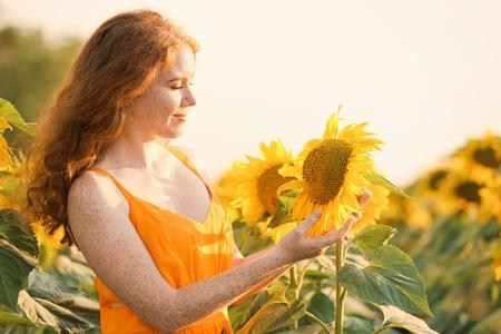 Beautiful redhead woman in sunflower field on sunny day Zdjęcie Seryjne