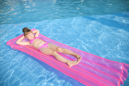 Cute little girl resting on inflatable mattress in swimming pool Фото со стока