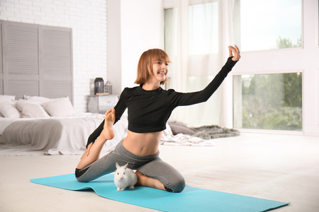 Sporty woman with bunny practicing yoga at home