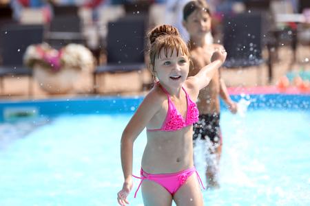 Linda chica jugando en la piscina el día de verano