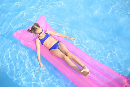 Cute little girl resting on inflatable mattress in swimming pool 版權商用圖片