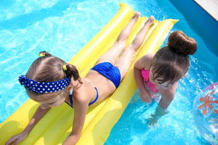 Cute children playing in swimming pool on summer day Reklamní fotografie - 113781547