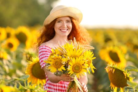 Beautiful redhead woman in sunflower field on sunny day Standard-Bild