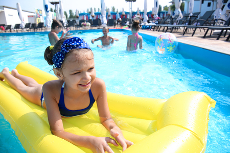 Cute girl swimming in pool on summer day