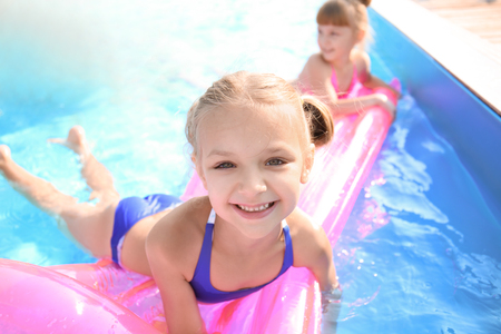 Cute children swimming in pool on summer day Stok Fotoğraf - 113781708