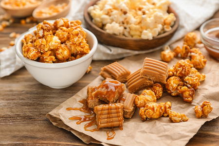 Delicious popcorn, sauce and caramel on wooden background Фото со стока