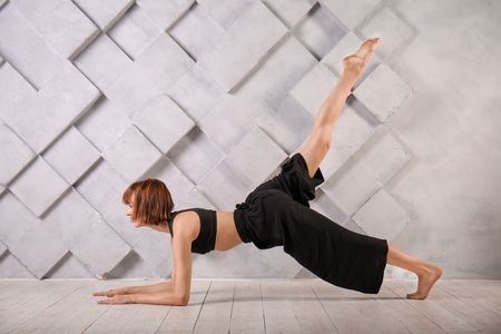 Sporty woman practicing yoga indoors