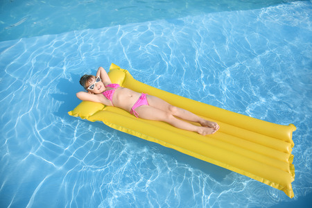 Cute little girl resting on inflatable mattress in swimming pool Banco de Imagens - 113781906