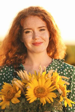 Beautiful redhead woman in sunflower field on sunny day Stok Fotoğraf