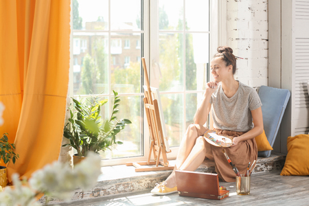 Female artist waiting for inspiration near window in workshop