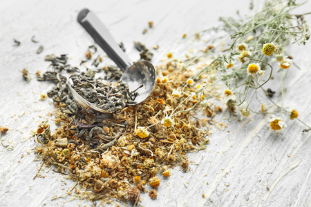 Tea strainer with dried chamomile flowers on wooden table Imagens