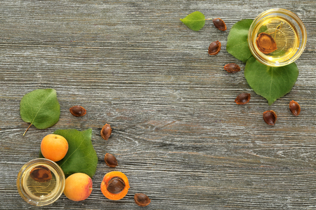 Bowls with essential oil and fresh apricots on wooden table