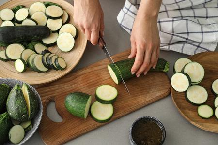 Woman cutting zucchini in kitchen