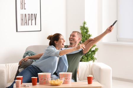 Couple fighting for remote control while watching TV at home