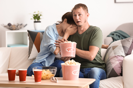 Couple eating popcorn while watching soap opera at home Imagens