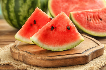 Board with delicious sliced watermelon on wooden table