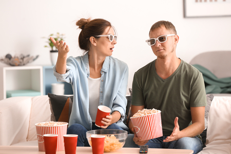 Couple eating popcorn while watching TV at home Stock Photo - 113796504