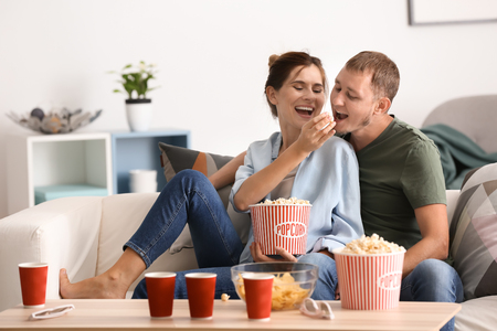 Couple eating popcorn while watching TV at home