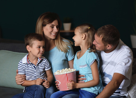 Happy family eating popcorn while watching TV in evening Stockfoto - 113796971