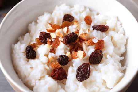 Bowl with delicious rice pudding, nuts and raisins, closeup