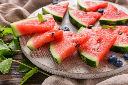 Wooden board with sweet watermelon slices on table, closeup