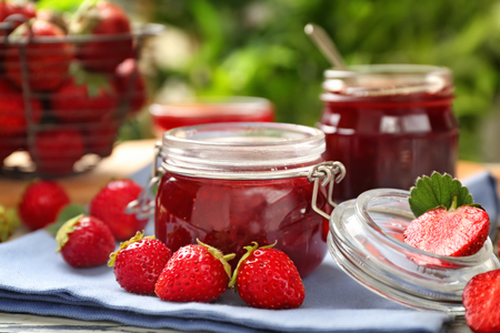 Glass jar with delicious strawberry jam on table Stock fotó