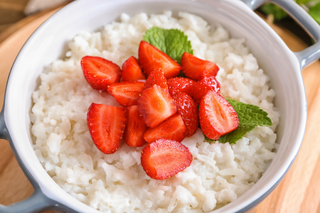 Bowl with delicious rice pudding and strawberry, closeup