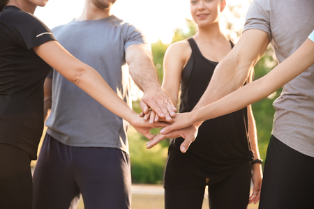 Group of sporty people putting hands together outdoors