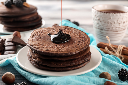 Pouring of sweet sauce onto delicious chocolate pancakes on table