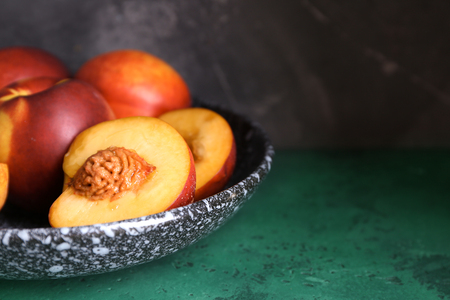 Plate with fresh peaches on green table, closeup