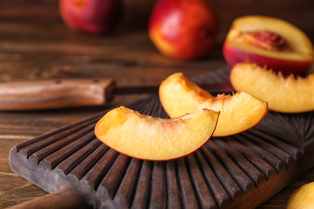 Board with fresh sliced peaches on wooden table, closeup