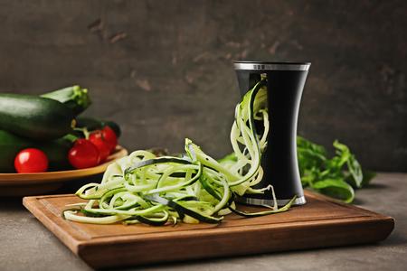 Spiralizer with zucchini noodles on kitchen table Standard-Bild