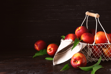 Basket with fresh peaches on wooden table