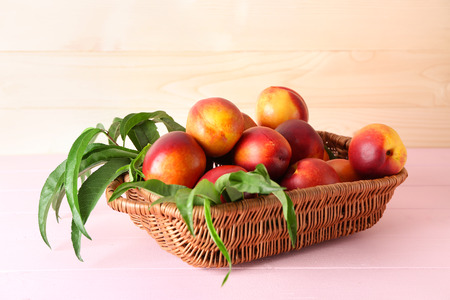 Wicker basket with fresh sweet peaches on color table