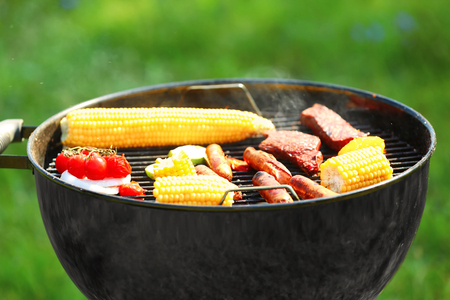 Tasty meat with vegetables and sausages cooking on barbecue grill outdoors