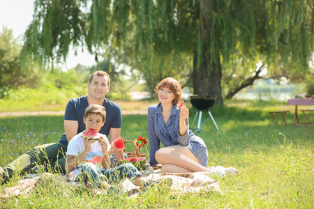 Happy family eating watermelon on summer picnic in park Stock Photo