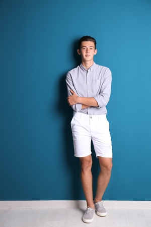 Young handsome man near color wall