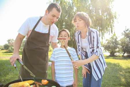 Family cooking tasty food on barbecue grill outdoors