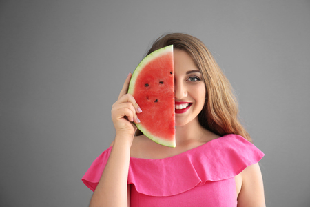 Beautiful young woman with slice of tasty watermelon on grey background
