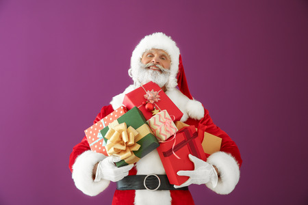 Santa Claus with gift boxes on color background