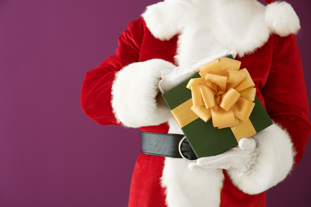 Santa Claus with gift box on color background, closeup