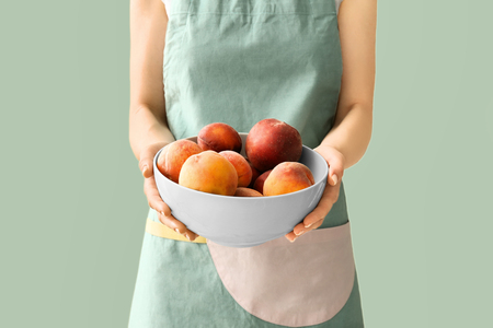 Woman holding bowl with fresh peaches on color background