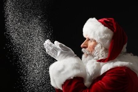 Portrait of Santa Claus playing with snow on dark background