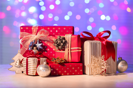 Beautiful Christmas gift boxes with decorations on table against blurred lights