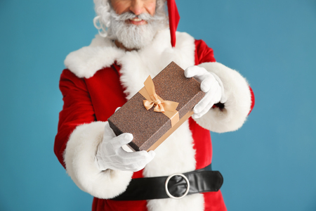 Santa Claus with gift on color background, closeup