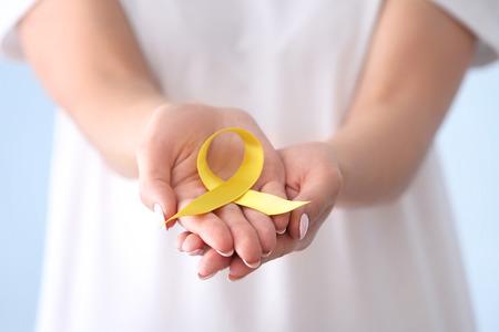 Frau, die gelbes Band, Nahaufnahme hält. Konzept zur Aufklärung über Krebs