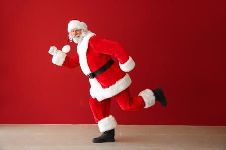 Running Santa Claus against color wall